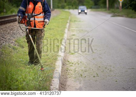Front View Of A Worker In Protective Clothing With A Petrol Lawn Mower On Wheels Walking On A Lawn W