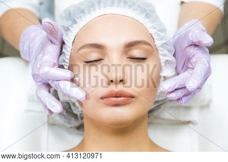 Facial Skin Care And Protection. A Young Woman At A Beauticians Appointment Looks In A Mirror. A Spe