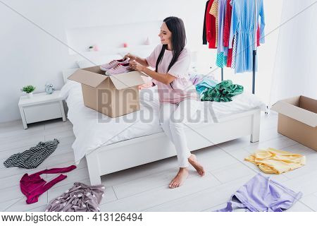 Photo Of Shiny Charming Young Woman Nightwear Sitting Bed Packing Boxes Sniekers Inside Indoors Home