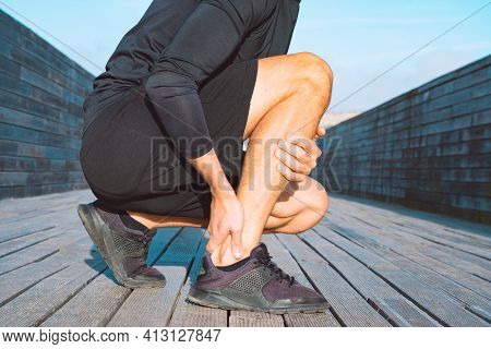 Running Injuries. Runner Suffering From Ankle Pain Or Achilles Injury. Ankle Twist Sprain Accident