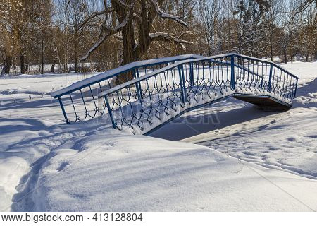 Landscape With Snow-covered City Park On A Bright Sunny Winter Day. Iron Pedestrian Bridge Over A Fr