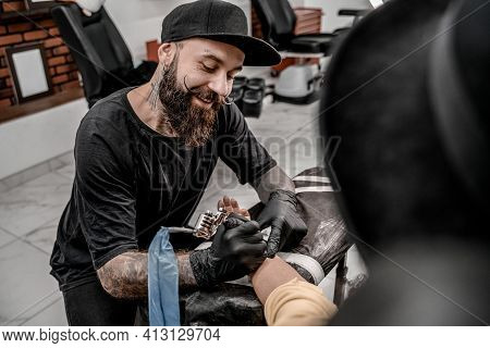 Male Tattoo Master Smiling Tattooing Female Client. Tattoo Machine And Lamp. Workplace Artist. Creat