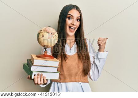 Beautiful brunette young woman holding pile of books and vintage world ball pointing thumb up to the side smiling happy with open mouth