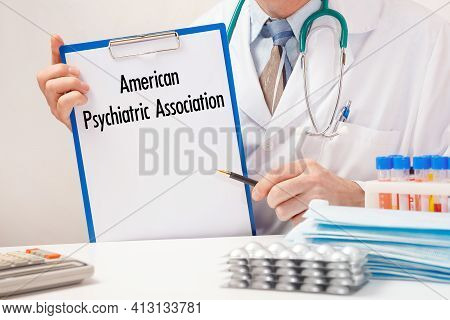Doctor Holds Paper With Inscription - American Psychiatric Association, Stethoscope And Pills On Tab