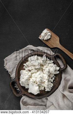 Fresh Cottage Cheese On A Wooden Plate With Spatula Top View. Dark Background With Gray Sackcloth