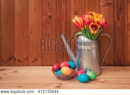 Easter Concept. Colorful Tulips In Watering Can And Easter Eggs In Wicker Basket On Wooden Table. Vi