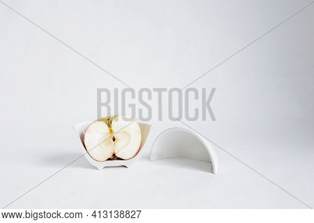 Sliced half Of An Apple In A Broken Half Of A Ceramic Small Platter On A White Background. Place F