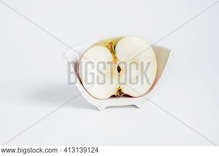 Sliced half Of An Apple In A Broken Half Of A Ceramic Small Platter On A White Background. Concept