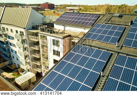 Aerial View Of Solar Photovoltaic Panels On A Roof Top Of Residential Building Block For Producing C