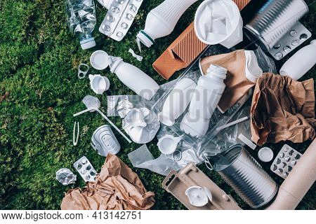 Food Plastic Packaging, Trash On Green Moss Background After Picnic In Forest. Top View. Copy Space.