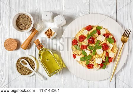Baked Feta Cheese Fusilli Pasta With Cherry Tomatoes And Basil On A White Plate On A Wooden Table, F