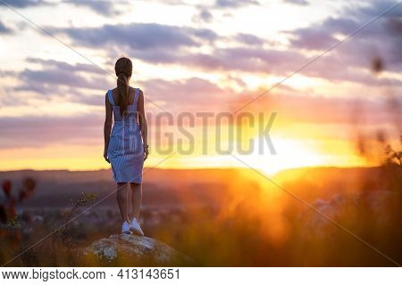 Dark Silhouette Of A Young Woman In Summer Dress Standing Outdoors Enjoying View Of Nature At Sunset