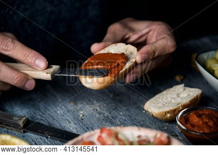 closeup of a young caucasian man preparing a vegan appetizer, by spreading a vegan version of the spanish sobrasada, made with sun-dried tomato and almonds, on a toasted halved bread bun