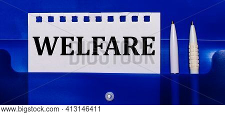 On A Blue Background, White Pens And A Sheet Of Paper With The Text Welfare