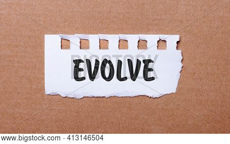 On A Brown Background, White Paper With The Inscription Evolve
