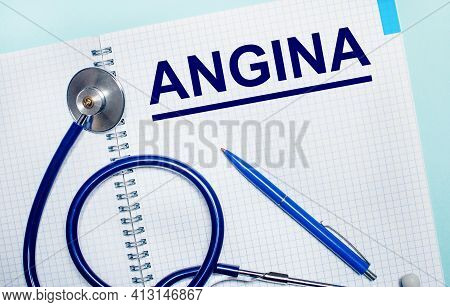 On A Light Blue Background, An Open Notebook With The Word Angina, A Blue Pen And A Stethoscope. Vie