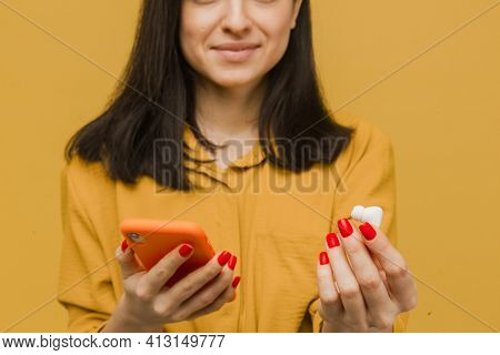 Close Up Photo Of Young Female Holds Earpods And Smartphone Looks So Kind And Happy. Wears Yellow Sh