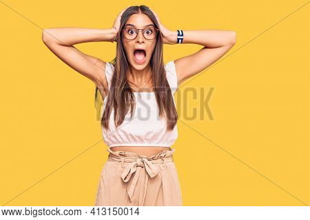 Young hispanic woman wearing casual clothes and glasses crazy and scared with hands on head, afraid and surprised of shock with open mouth