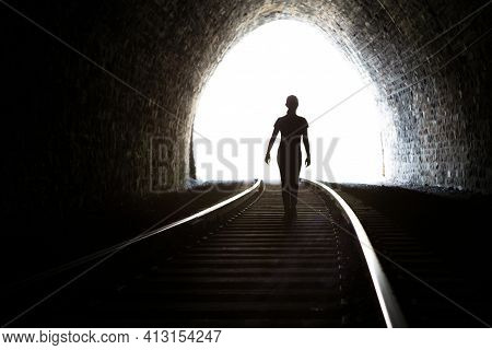 Silhouette Of A Girl Coming Out Of The Tunnel. Light At The End Of The Tunnel. Railway Rails In The