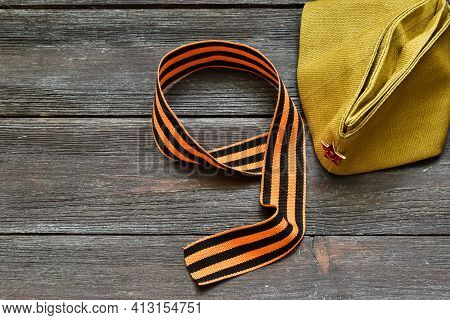 May 9. St. George Ribbon In The Form Of 9 And A Military Cap On A Wooden Background. The Traditional