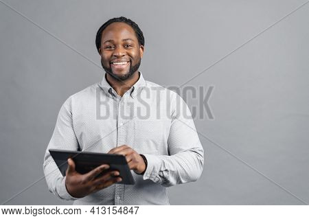 Cheerful African-american Young Man With Dreadlocks Holding A Digital Tablet, Testing Computer App,