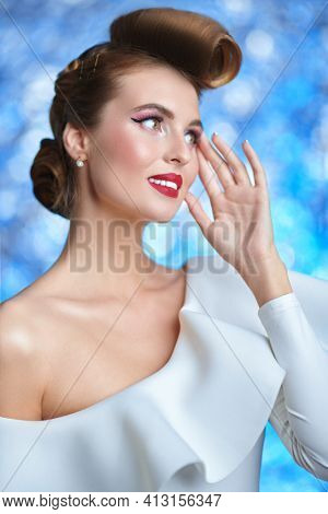 Charming woman in elegant white dress is smiling dreamy. Pin-up style in clothes, hair and make-up. Christmas look.