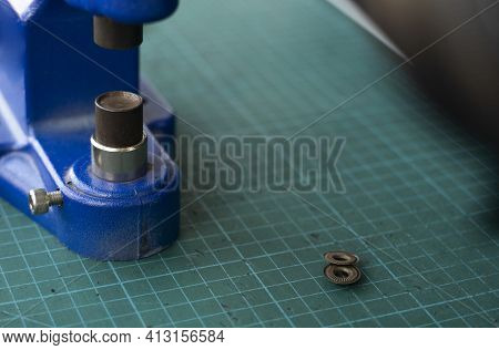 Artisan Using Hand Press For Setting Snaps In Leather For Makes A Wallet. Hand Pressure Snap Pressin