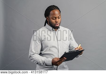 Concentrated African-american Young Man With Dreadlocks Holding A Folder, Taking Notes, Focused Blac