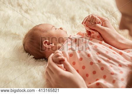 Mother's Hands Holding Newborn Baby Palms. Close Up Portrait Of Faceless Mommy With Her Newborn Baby