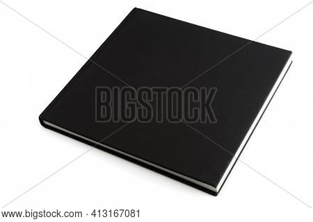 Black book lying on white surface, isolated with shadows