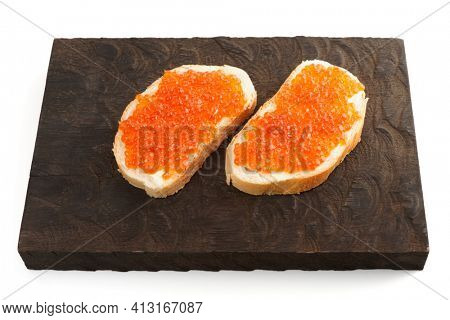 Open-face sandwiches with salmon roe on wooden serving board, isolated on white