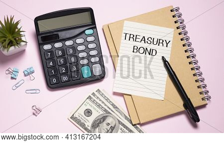 Paper With Treasury Bonds On A Table And Calculator.