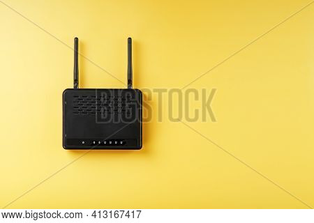 Wi-fi Router In Black On A Yellow Background With Free Space.