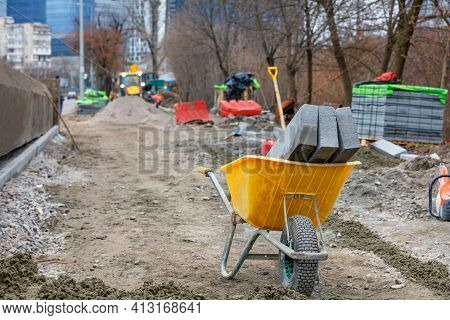 Construction Yellow Wheelbarrow And Curb Concrete Blocks At The Sidewalk Repair Construction Site Ag