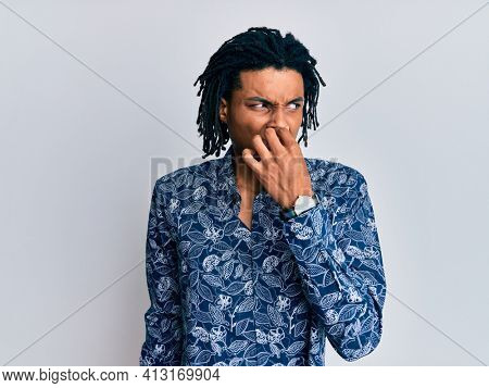 Young african american man wearing 80s style shirt smelling something stinky and disgusting, intolerable smell, holding breath with fingers on nose. bad smell