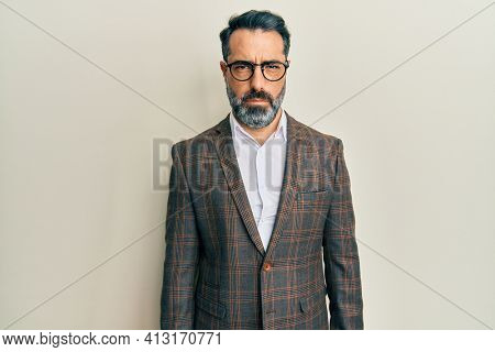 Middle age man with beard and grey hair wearing business jacket and glasses skeptic and nervous, frowning upset because of problem. negative person.