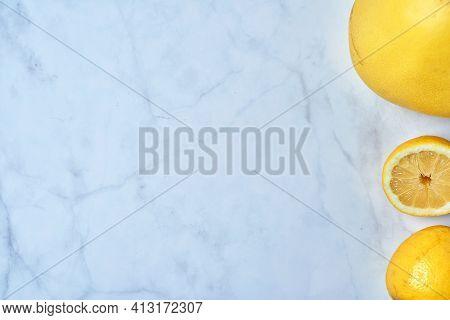 Top View Of Fresh Lemons On Kitchen Marble. Grapefruit, Open Lemon And Whole Lemon, Antioxidant Vita