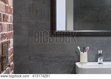 Loft-style Bathroom Interior Details. Neutral Gray Porcelain Stoneware, Brick Wall And Mirror Above