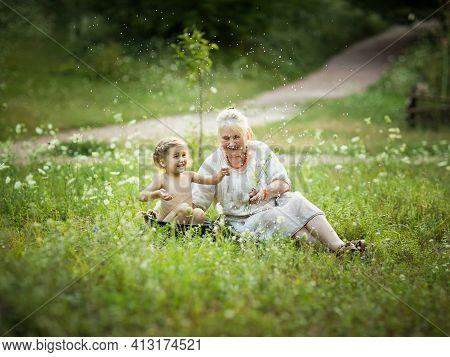 Old Woman Bath Little Girl In A Basin Outdoor In Summer Day Around Flowers