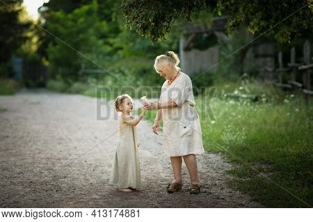 Grandmother And Granddaughter Walk Around The Park In White Vintage Clothes. Old Woman Plays With Li