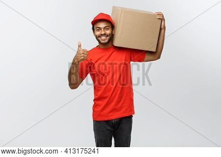 Delivery Concept - Portrait Of Happy African American Delivery Man Holding A Box Package And Showing