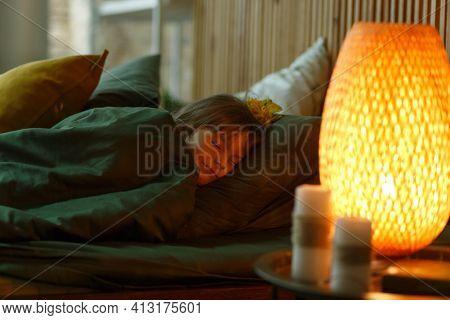 Cute Little Girl Lying Under Blanket In Her Bed