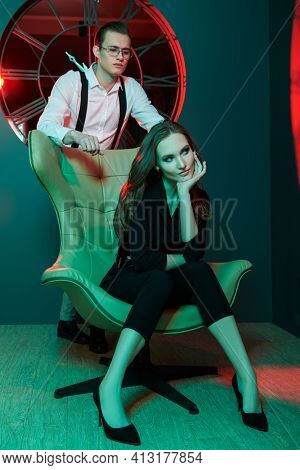 Handsome young man poses with woman sitting on an armchair in a luxury apartment. Glamorous lifestyle. Fashion shot in greena and red lighting.