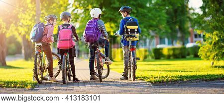 Children With Rucksacks Riding On Bikes In The Park Near School. Pupils With Backpacks Outdoors