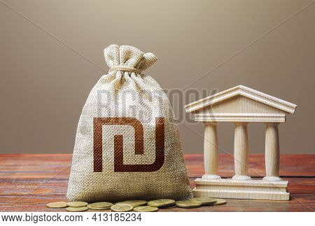 Israeli Shekel Money Bag And Bank / Government Building. Monetary Policy. Tax Collection And Budgeti