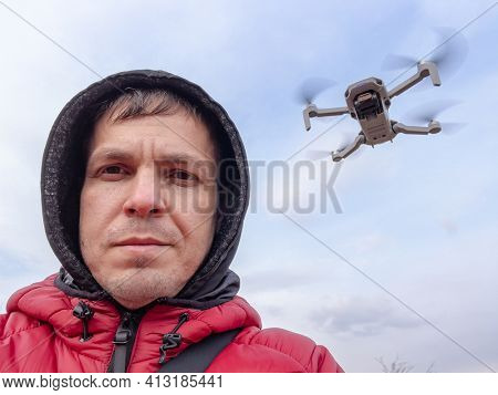 Man controls the flying drone. Grey drone with camera flying in the air outdoors. Little drone flying outside in sky.