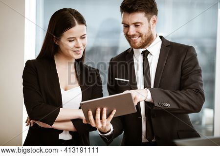 Successful business and modern technology concept. Young businesswoman and happy smiling businessman working together using tablet computer. Two colleagues man and woman teamwork indoors