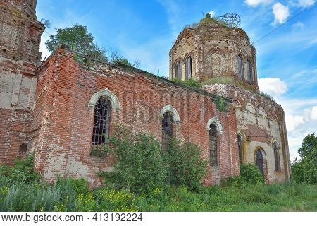 Part Of A Ruined Temple With A Bell Tower Overgrown With Grass Against The Background Of A Cloudy Sk