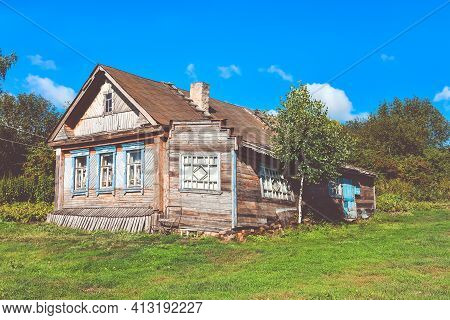 Wooden House In The Village Against The Sky Surrounded By Greenery