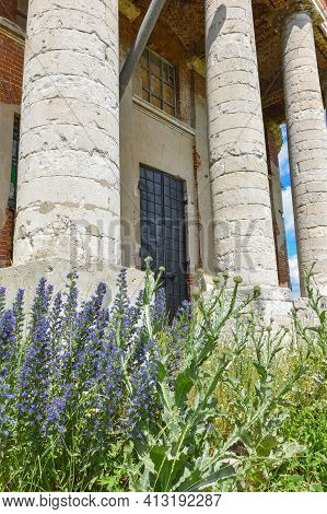 Part Of The Entrance With Brick Columns In The Background, Grass And Flowers In The Foreground
